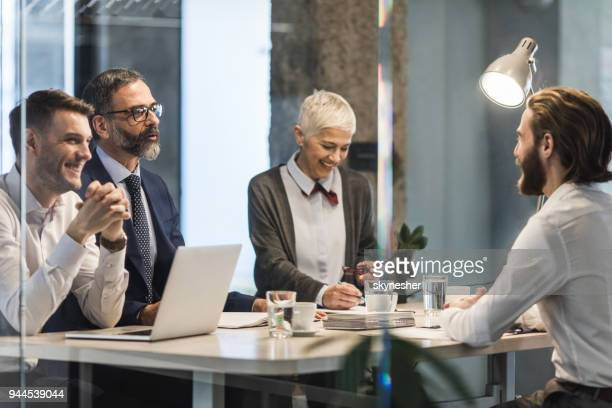 Team of business people talking to a candidate on a job interview in the office.