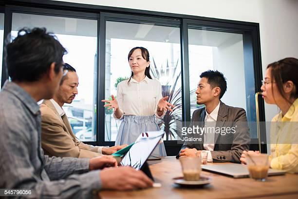 ビジネスマンとテーブルの周りの女性のチーム - ビジネスウェア ストックフォトと画像