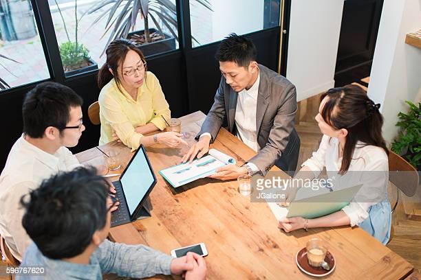ビジネスマンとテーブルの周りの女性のチーム - ミーティング ストックフォトと画像