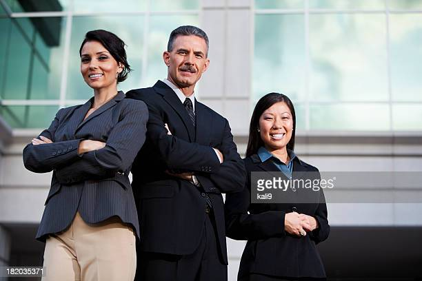 Team of businesspeople standing outside office building