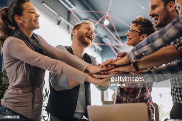 equipe de empresários alegre, reunindo as mãos na unidade. - cinco pessoas - fotografias e filmes do acervo