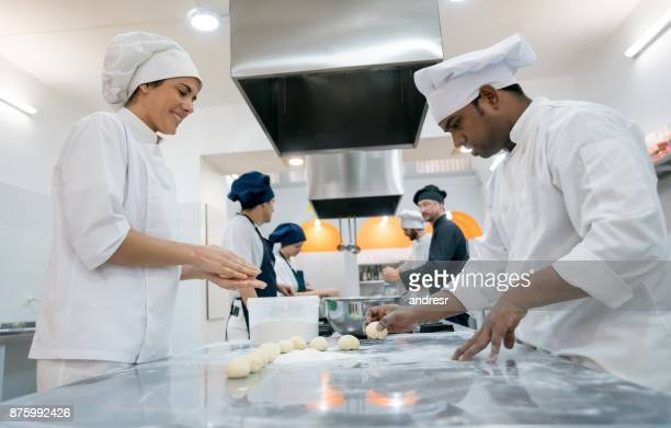 Team of chefs kneading pastry to make a bread smiling