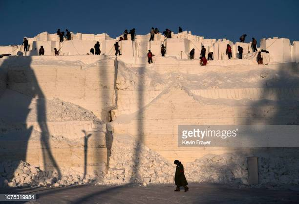 A team of Chinese laborers carve into a large snow mound in preparation for the Harbin Ice and Snow Festival on December 20 2018 in Harbin China The...
