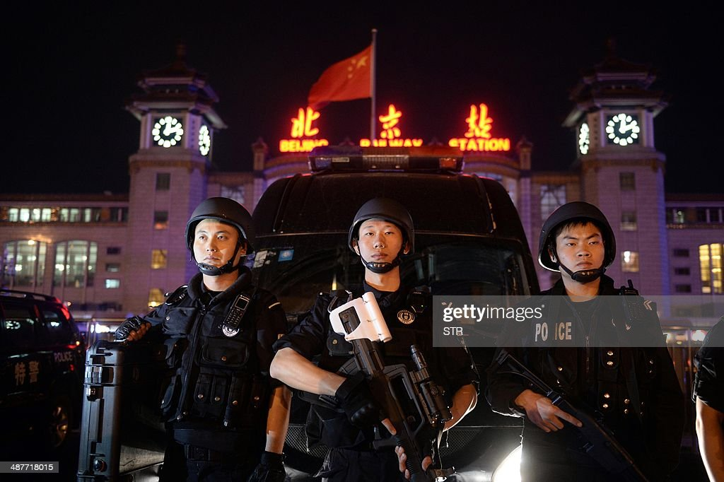 A team of Chinese special police take up position during a drill outside the railway station in Beijing on the early hours of May 2, 2014. Chinese President Xi Jinping ordered a crackdown after a stabbing spree and explosion at a railway station in the restive Muslim-majority region of Xinjiang left two attackers and a civilian dead and 79 wounded, state media said. CHINA