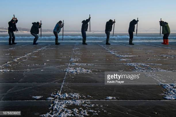 A team of Chinese workers use ice picks to dislodge large cubes of ice that will be used in the making of ice sculptures from the frozen Songhua...