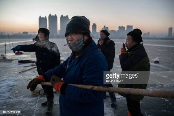 A team of Chinese workers wait to move large ice cubes that will be used in the making of ice sculptures from the frozen Songhua River in preparation...