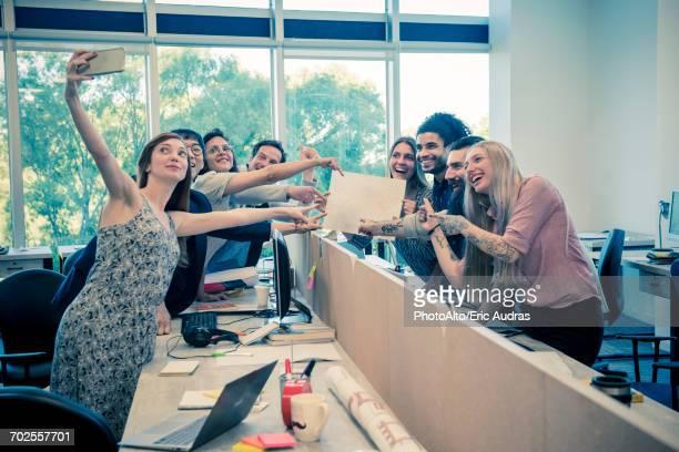 team of colleagues taking a selfie together in shared office - grupo mediano de personas fotografías e imágenes de stock