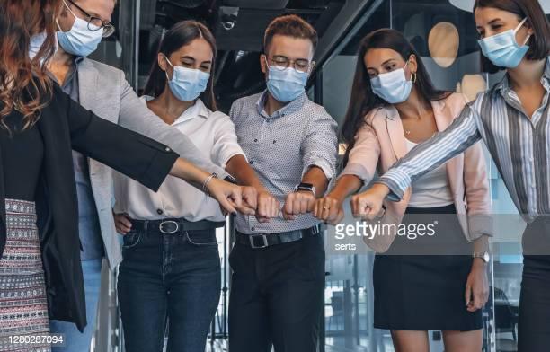 équipe de collègues avec le masque de visage joignant leurs mains ensemble dans l'unité pendant la pandémie - solidarité photos et images de collection