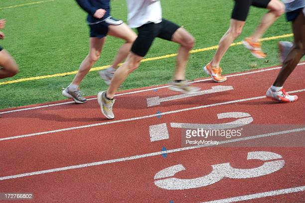 Team of Competitive Athletes Sprinting on Running Track
