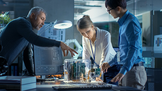 Team of Computer Engineers Lean on the Desk and Choose Printed Circuit Boards to Work with, Computer Shows Programming in Progress. In The Background Technologically Advanced Scientific Research Center. 968289874