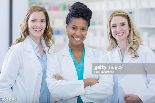 Team of confident female pharmacists smiling for photo in neighborhood pharmacy