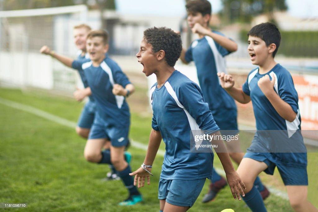 Team von selbstbewussten jungen männlichen Fußballern läuft auf dem Feld : Stock-Foto
