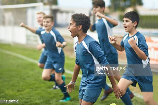 team of confident young male footballers running onto field - termine sportivo foto e immagini stock
