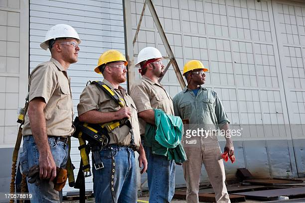 team of construction workers with harnesses - safety harness stock photos and pictures