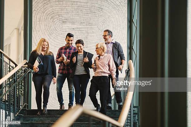 Team of creative business people moving downstairs at office