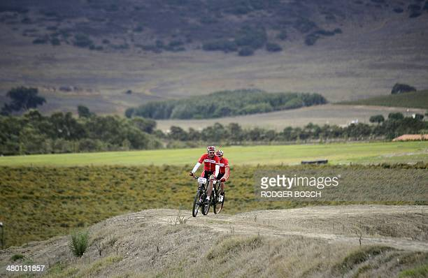 A team of cyclists taking part in the 2014 Cape Epic mountain bike race ride past vineyards near the start of the Prologue stage at Meerendal wine...