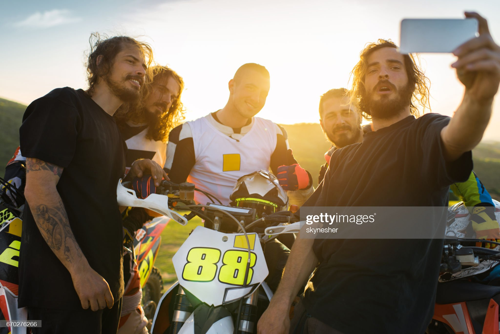 Team of dirt bike racers taking selfie at sunset. : Stock Photo