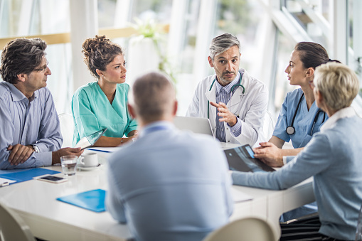 Team of doctors and business people talking on a meeting at doctor's office. 1002020774