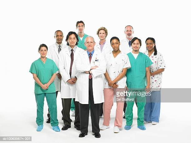Team of doctors and nurses standing on white background, portrait