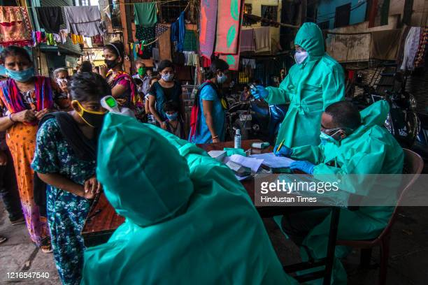 Team of Doctors check the temperature and pulse rate of a local residents at a COVID-19 coronavirus testing drive inside the Dharavi slums during a...