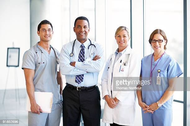 team of doctors in hospital lobby - group of doctors stock pictures, royalty-free photos & images