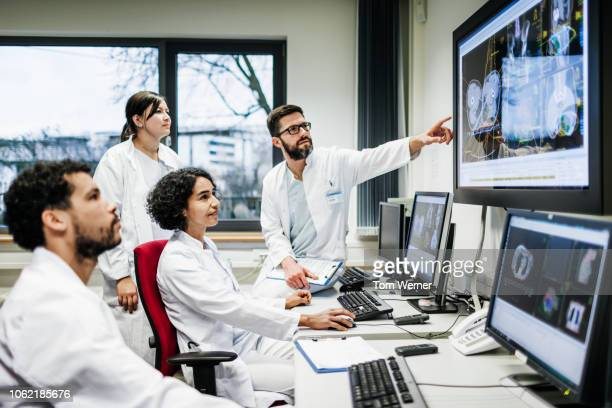 team of doctors looking at lab results - onderzoek stockfoto's en -beelden