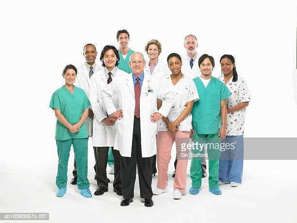 Team of doctors, nurses and surgeons standing on white background, portrait