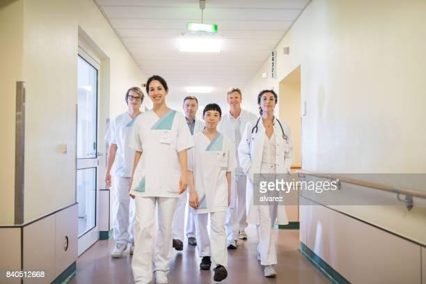 wandern im krankenhausflur ärzteteam - krankenpflegepersonal stock-fotos und bilder