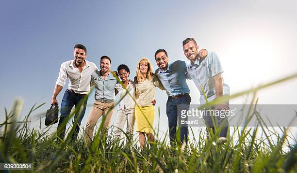 Team of embraced business people in a meadow.