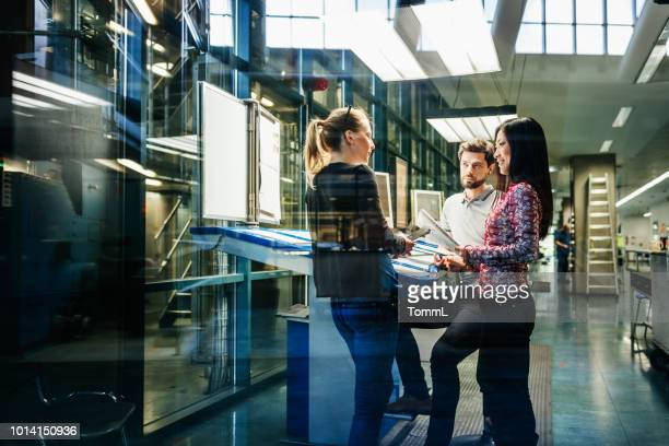 team of engineers having discussion at desk - industry stock pictures, royalty-free photos & images