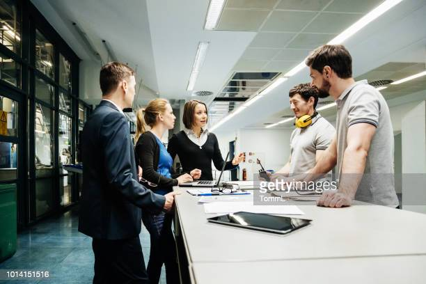 team of engineers holding meeting in factory - industry stock pictures, royalty-free photos & images