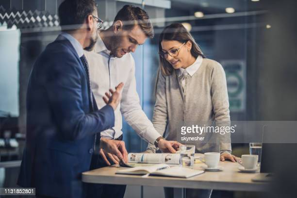 team of entrepreneurs reading a magazine in the office. - glass magazine stock photos and pictures