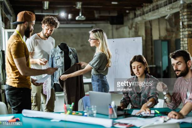 team of fashion designers working in clothing design studio. - fashion industry stock pictures, royalty-free photos & images