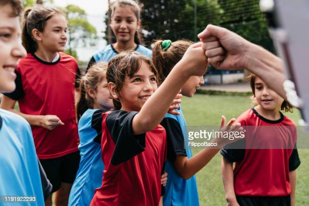 team of female and male kids together on a soccer field - team sport stock pictures, royalty-free photos & images