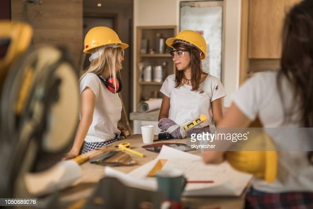 Team of female construction workers talking during home renovation process.