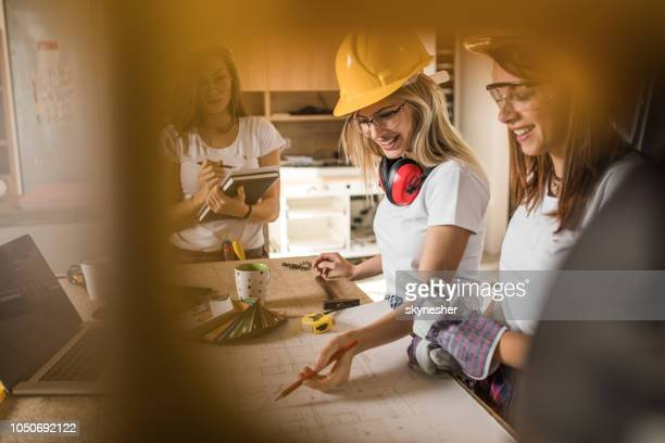 Team of female manual workers examining housing plans at construction site.