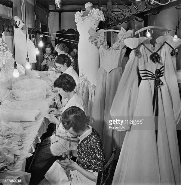 Team of female seamstresses work on the remodelling of customers dresses from last year to be recycled in to new outfits for the new season in work...