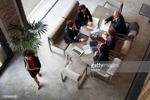 team of financial advisors planning with business colleagues during meeting at law firm - mid adult stock pictures, royalty-free photos & images