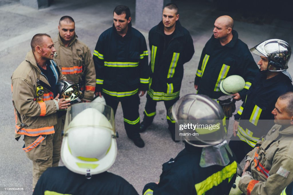 Team of firefighters listening to instructions : Stock Photo