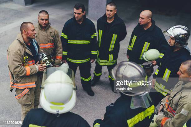 team of firefighters listening to instructions - firefighter stock pictures, royalty-free photos & images