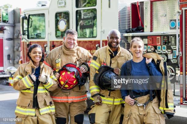 消防車の前に立つ消防士のチーム - 消防士 ストックフォトと画像