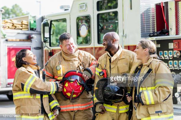 team of firefighters standing in front of fire truck - firefighter stock pictures, royalty-free photos & images