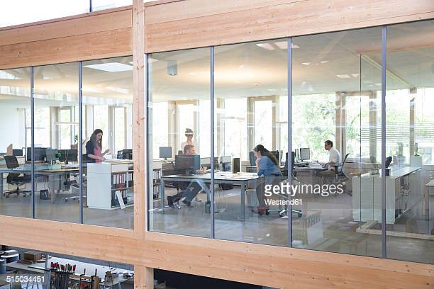 team of five business people at workplaces in modern office - open plan stock pictures, royalty-free photos & images