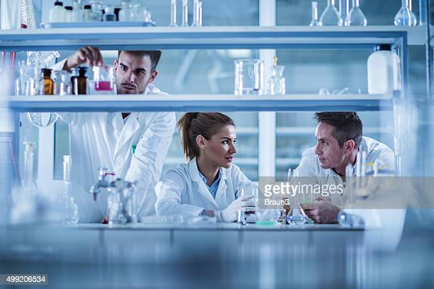 Team of forensic scientists cooperating while working in laboratory.