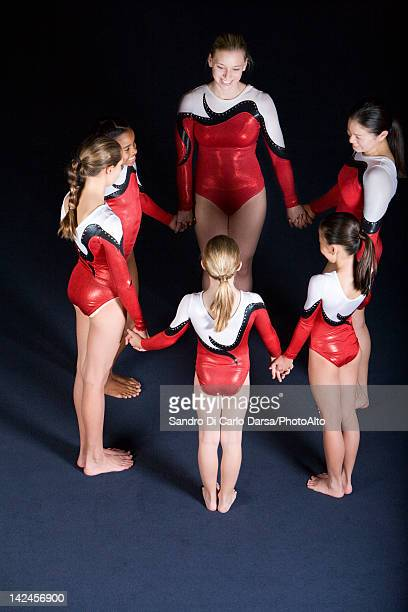 team of gymnasts standing in circle, holding hands - little girls leotards stock photos and pictures