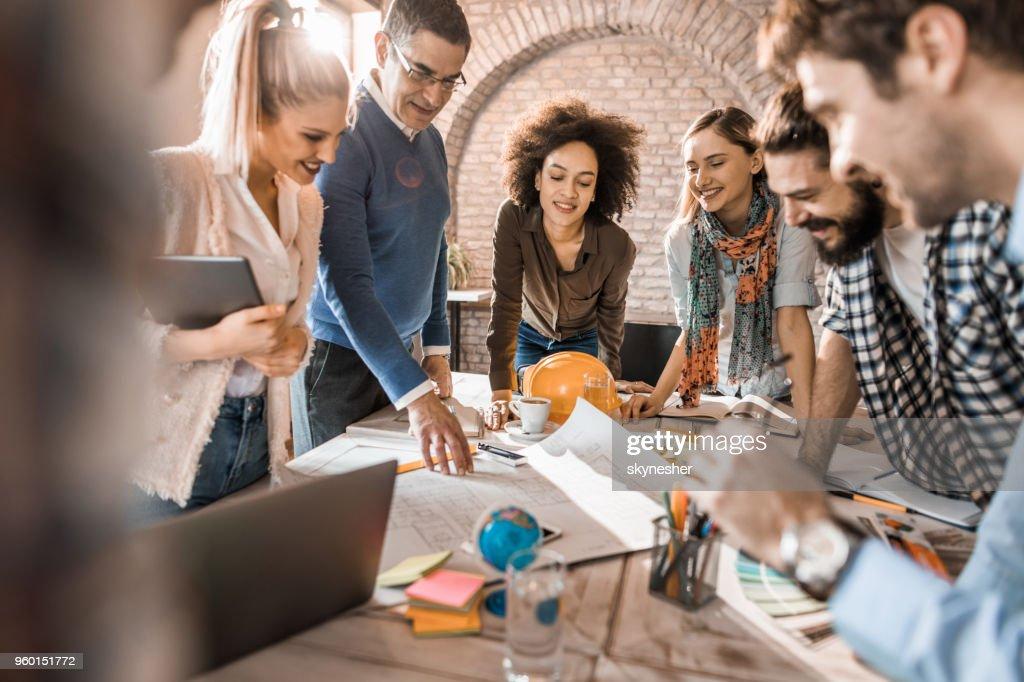 Team von glücklich Architekten Entwürfe auf einem Treffen im Büro zu analysieren. : Stock-Foto