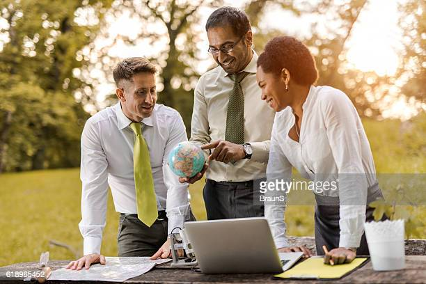 Team of happy business colleagues looking at globe in nature.