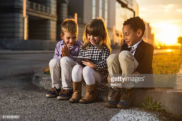 Team of happy business kids using digital tablet at sunset.