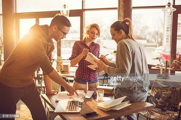 Équipe d'étudiants heureux amis travaillant ensemble tout en étudiant au café.