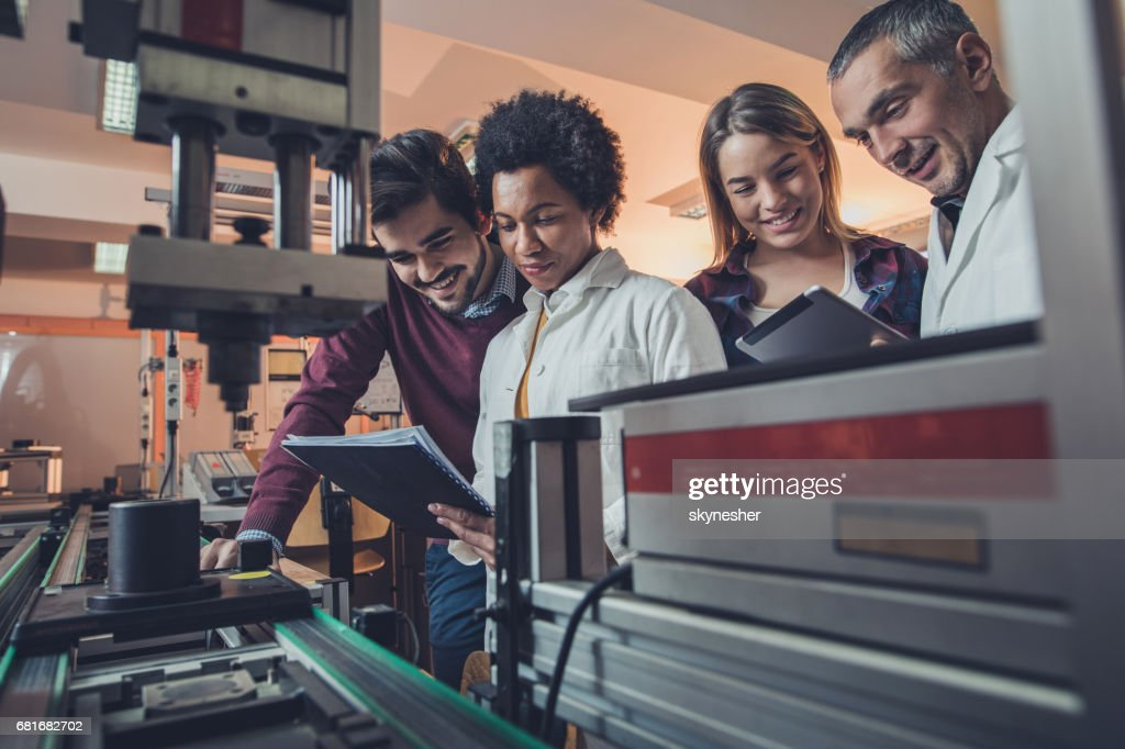 Team of happy engineers analyzing data of a manufacturing machine. : Stock Photo